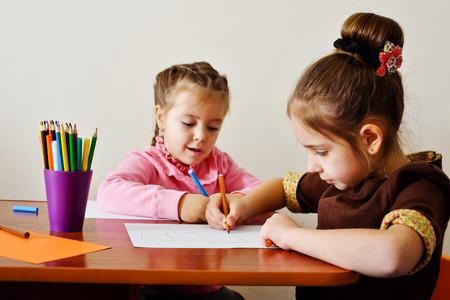 school work: two preschool girls are drawing at the table