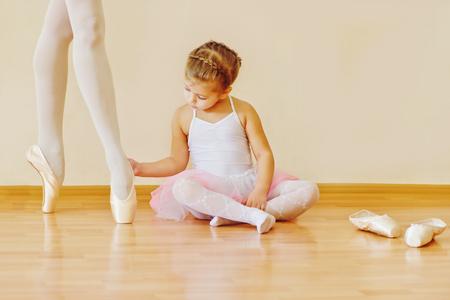 la niña que mira en los pies de instructor en la escuela de ballet