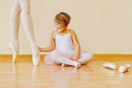 ballerina costume: little girl looking on feet of trainer in ballet school Stock Photo