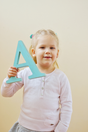 fundamentals: toddler girl is standing with letter A Stock Photo