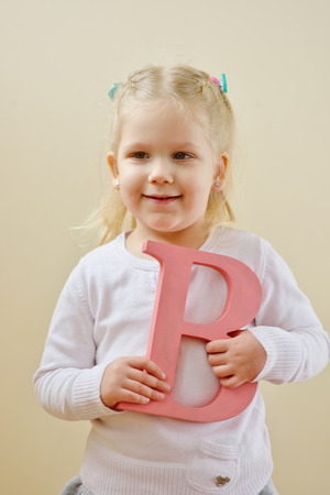 fundamentals: toddler girl is standing with letter B