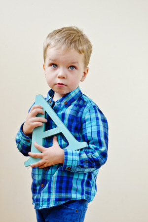 fundamentals: toddler boy is standing with letter A