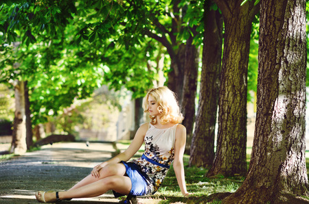 lady wearing dress sitting in the park photo