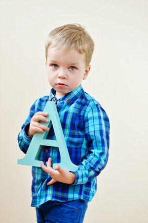 fundamentals: toddler blonde boy with a wooden letter A
