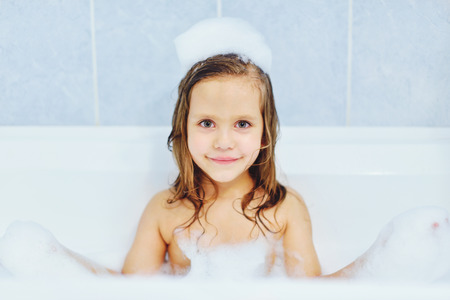 little  girl in the bathroom playing with foam Stock Photo