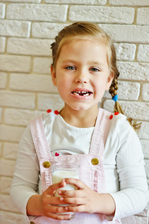 milk tooth: funny little girl lost her milk tooth with glass of milk