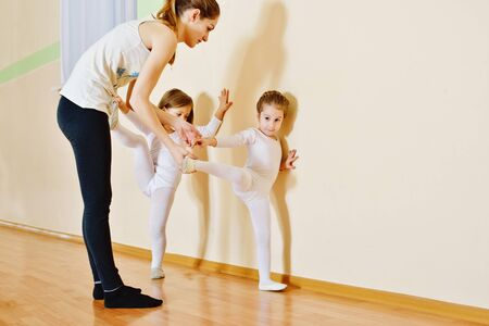 girl studying: trainer and two little girls in gymnastic class