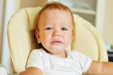 tearful: little baby is crying and sitting on the chair