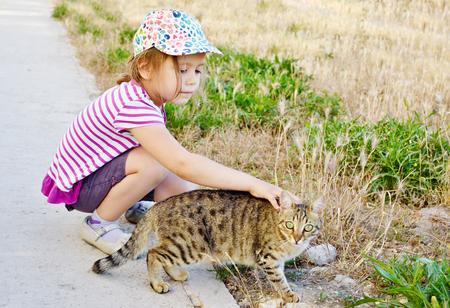 flatter: little girl petting  alley cat on the street Stock Photo