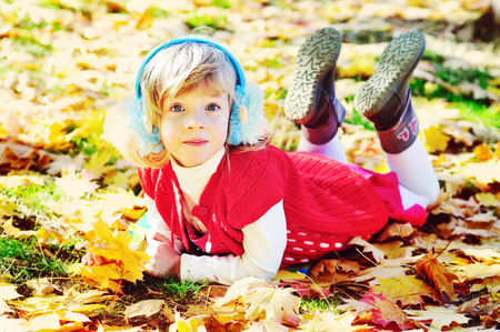 little girl in fall time on the foliage photo
