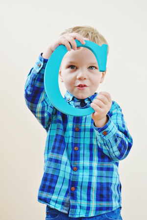 toddler blonde boy with a wooden letter c photo