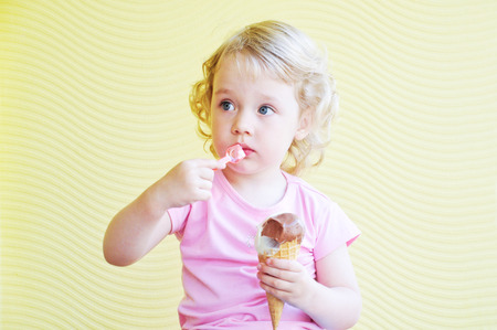 little girl  eating big ice cream cone in cafe photo