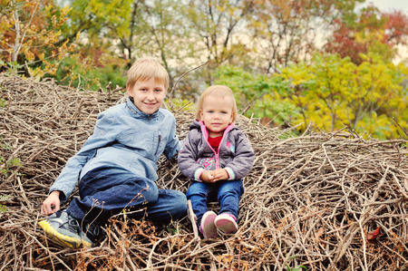 brother and little sister on the woods in fall photo