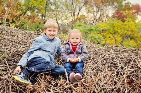 hermano y hermana pequeña en el bosque en otoño photo