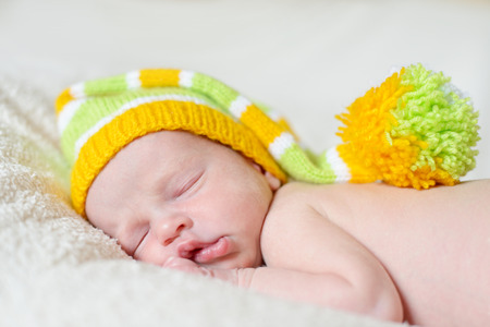 little sleeping newborn wearing a striped hat photo