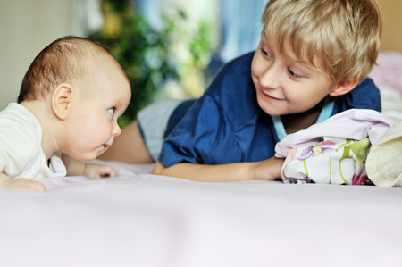 brother and baby sister on the bed, focus on baby Stock Photo