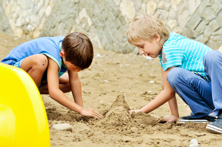 two funny boys playing sand in summer time photo