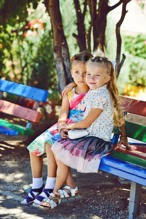 two happy little fashion girls are hugging outdoors photo