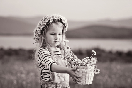 girl with daisies in basket and on the head photo