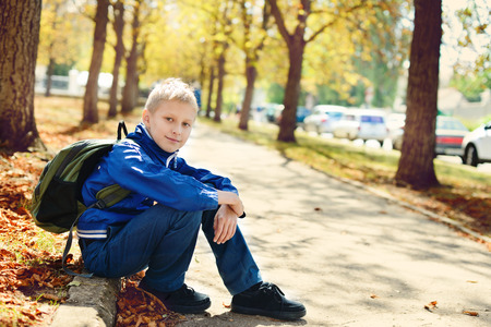 schoolboy with backpack after school in park photo