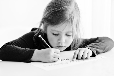 little girl is writing at the table