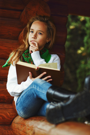 dreaming beautiful girl reading a book outdoors photo