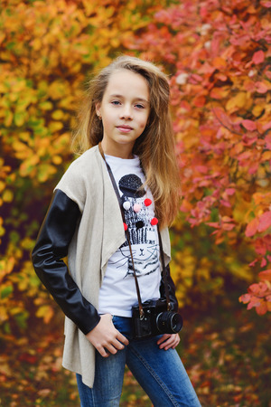 pretty preteen girl with old photocamera in fall time photo