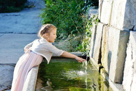 Adorable little girl in princess dress near the fountain outdoor photo
