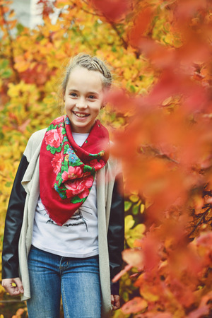 happy preteen girl  is standing near the fall bushes