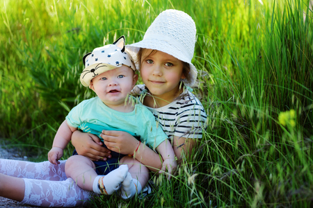 sister with baby brother on the green meadow photo