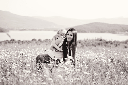 mother and daughter in field of daisies photo