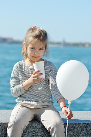 sweet little girl drinking cocoa next to the sea photo