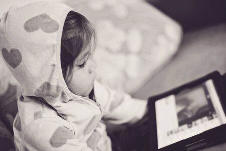 Cute toddler girl is using tablet pc photo
