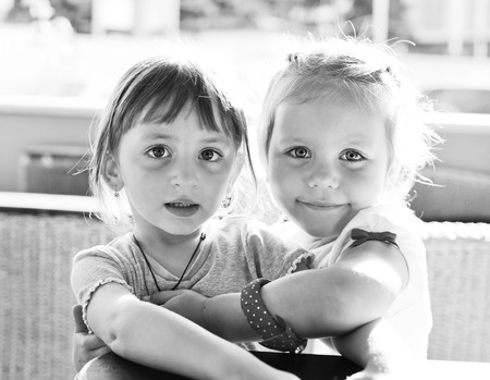 two sweet little  friends sitting and hugging photo