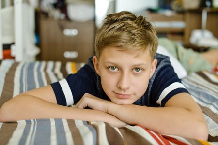 teen boy at home laying on the bed  免版税图像