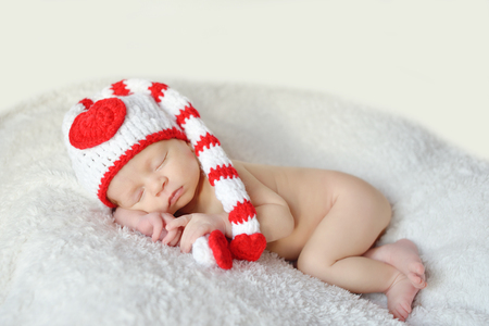 Newborn baby  sleeping and wearing a knitted hat Stock Photo