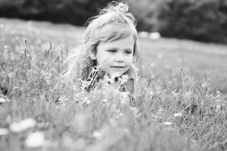 Toddler girl is relaxing on the meadow