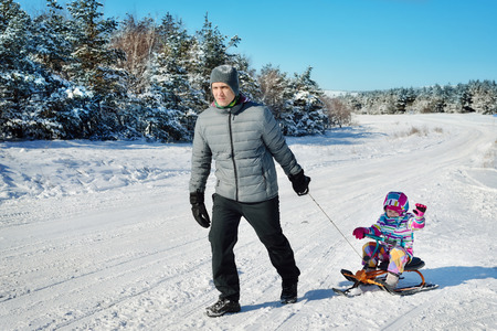 Father and daughter playing in winter on snow 스톡 콘텐츠
