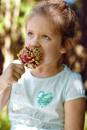 Cute little girl is eating candy apple  Stock fotó