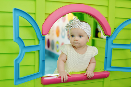 baby girl  looking out from plastic play house  Stock Photo