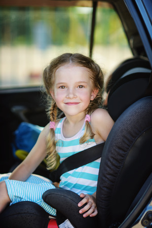 little girl in the car seat in summer time