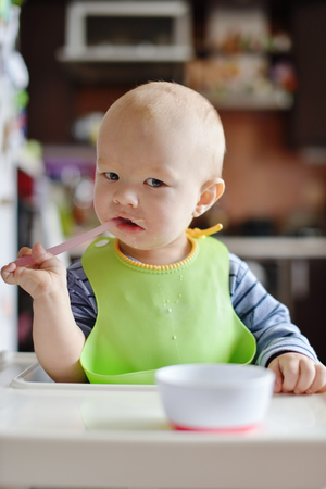 baby trying to eat on his own at home