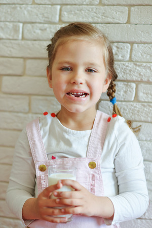 funny little girl lost her milk tooth with glass of milk