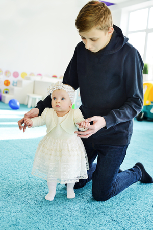 brother with baby girl wearing occasion dress Stock Photo