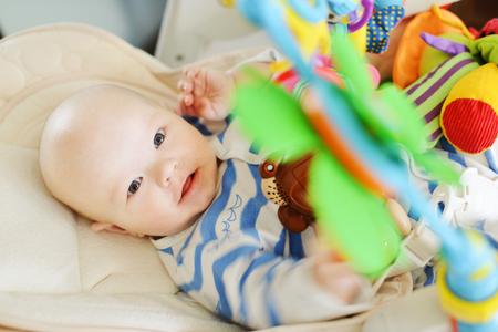 baby in uitsmijter stoel en speelgoed spelen