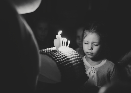 girl with birthday cake with caldles wishing in darkness