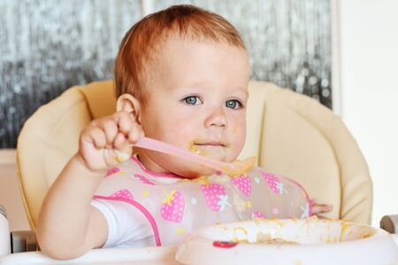 eating baby girl with spoon and dirty face Archivio Fotografico
