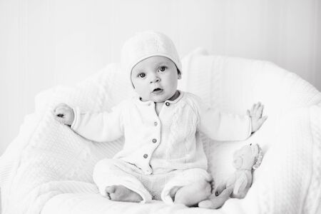 sweet baby wearing knitted suit is sitting on the arm-chair