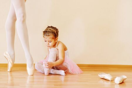 little girl looking on the legs of ballet teacher