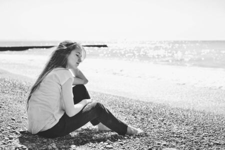 pensive teen girl sitting near the sea Archivio Fotografico